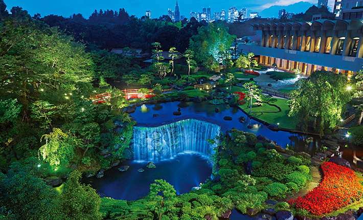 The illuminated Japanese garden by night. Tour d'Argent Tokyo is located on the second floor of the building in the farther right.